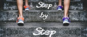 2 pairs of legs with trainers on climbing steps